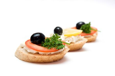 Mini sandwiches - bread with cream cheese, tomato, lemon, olives and parsley photo