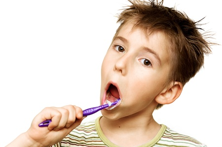 Beautiful boy brushing teeth, isolated on white photo