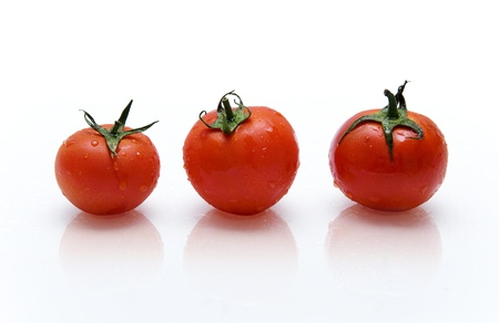 three red tomatoes with drops of water on the reflective surface photo