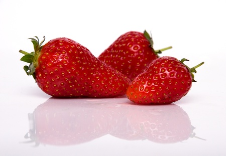 Three strawberries isolated on white background with reflection photo