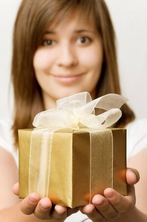 beautiful young teen girl with a gift  box in her hands. Focus on gift box. photo