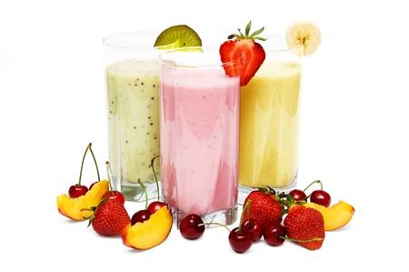 batidos de frutas: Batidos de frutas con cerezas, fresa y durazno aisladas sobre fondo blanco Foto de archivo