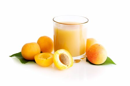 glass of apricot juice with apricots isolated on a white background