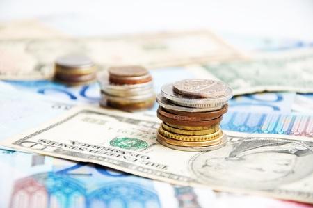 pounds money: Pilas de monedas mixtas sobre fondo de dinero de diferentes pa�ses