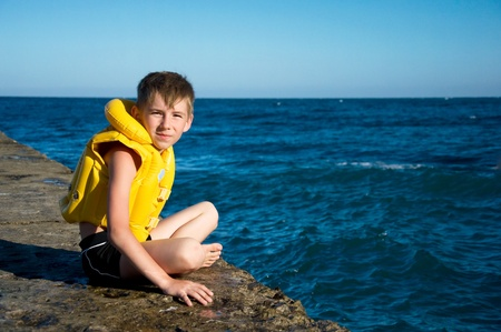 life jackets: boy wearing in yellow life jacket sits on a pier near  the sea