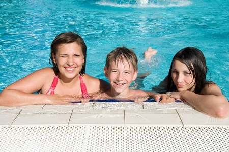 pool side: kids relaxing in a row on side of swimming pool