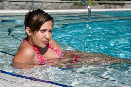 beautiful girl relaxing in the outdoor pool at the resort photo