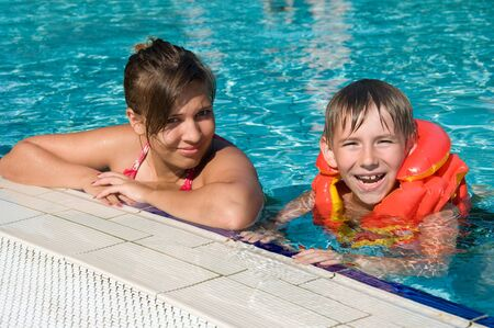 Smiling cute kids in a swimming pool in sunny day Stock Photo - 10104109