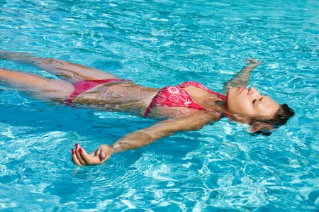 swimming to float: Young girl is swimming in a pool in sunny day Stock Photo
