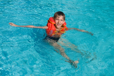 domestic life: Boy in life jacket is learning to swim in the swimming pool