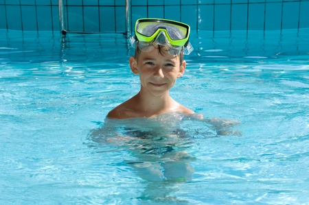 portrait of cute boy wearing in yellow goggles in a swimming pool photo