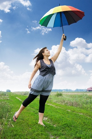 beautiful young girl with a colorful umbrella flying away