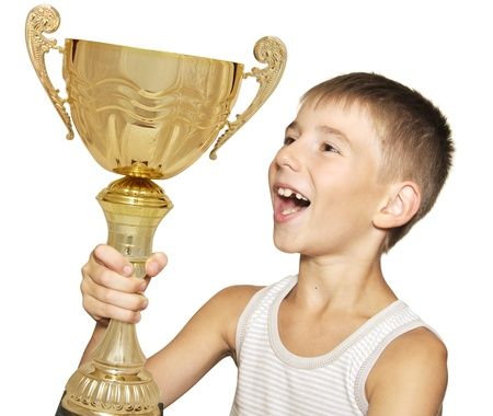 Portrait of an excited little champion with his trophy isolated against white background photo
