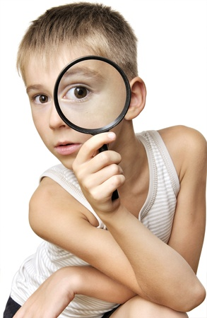 Beautiful boy looking through a magnifying glass isolated on a white background photo