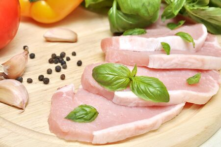 raw meat on a cutting board with basil and vegetables photo