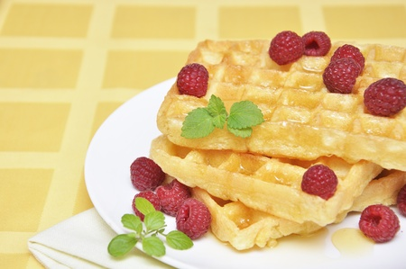Waffles with honey and raspberry on white plate photo