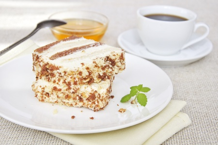 Sweet dessert. Two slices of cake on white plate with cup of coffe and honey photo