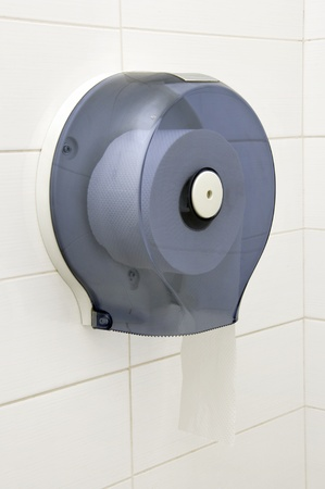 Bathroom tissue hanging on the wall  Toilet paper on white tiles photo