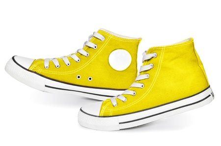 Pair of  new yellow sneakers isolated on white background