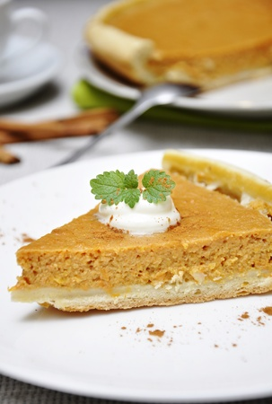 Slice of homemade pumpkin pie with whipped cream and mint served on white plate Stock Photo - 11005411