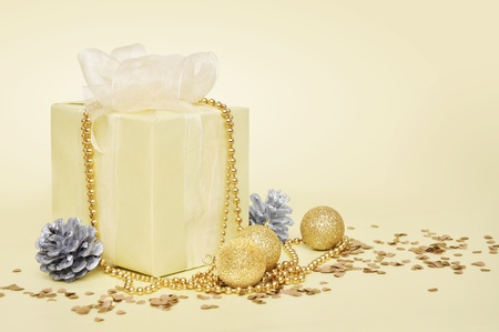 Yellow gift box with Christmas decoration on light background photo