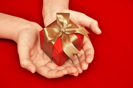 gift parcel: Small red gift in a female hand over red background Stock Photo