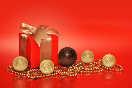 Red gift box with golden ribbon and cristmas decoration on red background photo