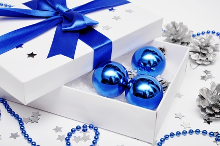 Open gift box with artificial snow and blue christmas decorations in it photo