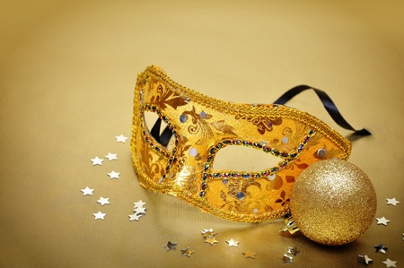 Carnival mask on golden background with silver confetti photo