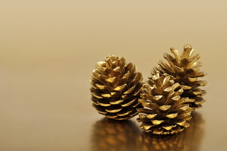 pine three: three golden pine cones over gold background