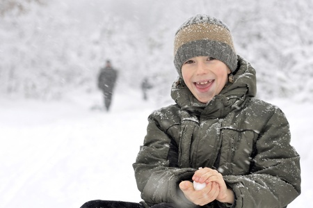 smiling boy makes a snowball. Walk in the snowy winter woods photo