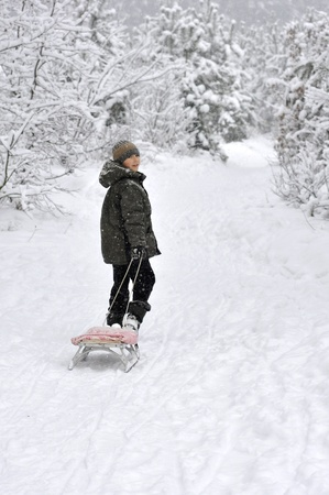 smiling boy walking with sleds in snow-covered winter forest photo