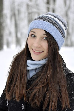 Portrait of beautiful smiling girl in snowy winter forest photo