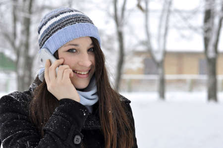 beautiful smiling girl talking on cell phone in snowy winter park photo