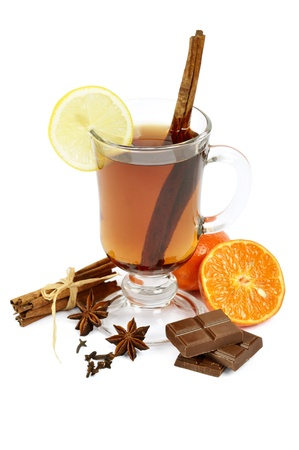 Mulled wine with chocolate, cinnamon, anise, lemon and orange over white photo