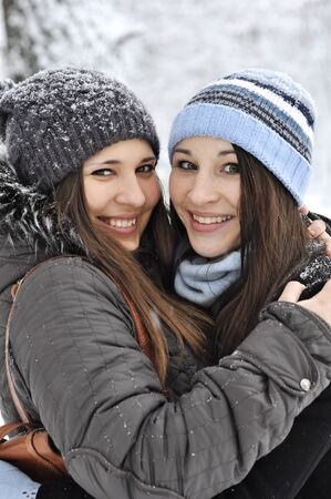 Two young girl wearing warm winter clothes in winter park photo
