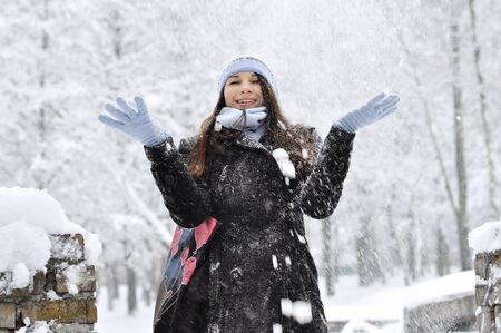 beautiful girl throwing snow in the air in winter park photo