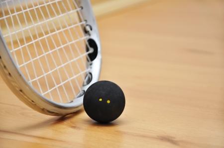 racquetball: Primer plano de una raqueta de squash y la pelota por encima de fondo de madera