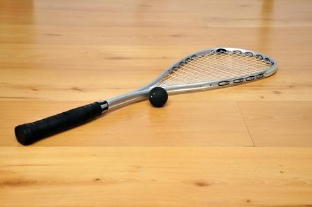 racquetball: una raqueta de squash y una pelota en el suelo