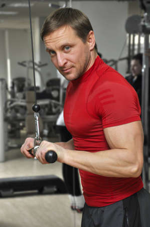tricep: health club: man in a gym doing weight lifting