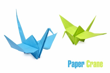 Traditional Japanese origami cranes made from blue and green paper over white background photo