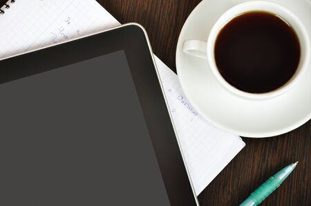 Workplace with  digital tablet, notebook, pen and cup of coffee on work table closeup photo