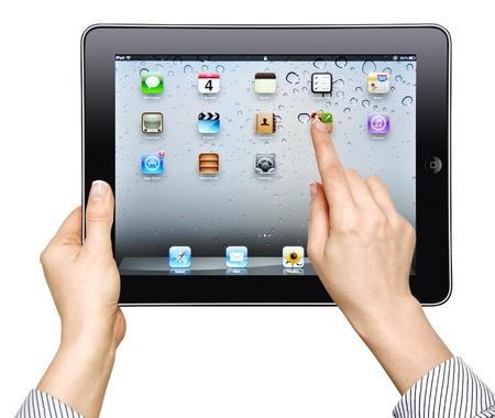 Kiev, Ukraine - April 03, 2012: Female hands holding Apple iPad (32Gb, wi-fi) with homepage on a screen. This second generation Ipad is designed and development by Apple inc.