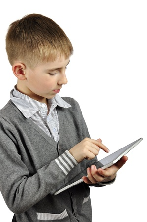 Portrait of a cheerful boy using a tablet computer against a white background photo