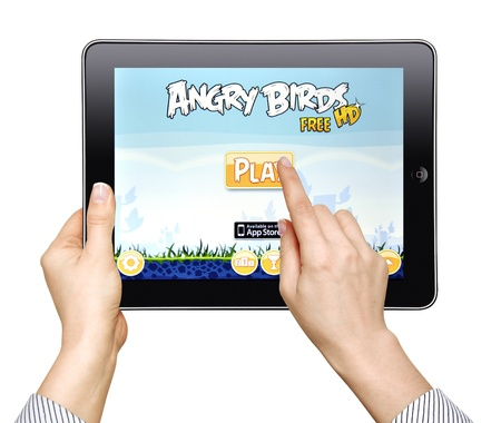 A woman  play in the game Angry Birds on Apple Ipad2 isolated on white background