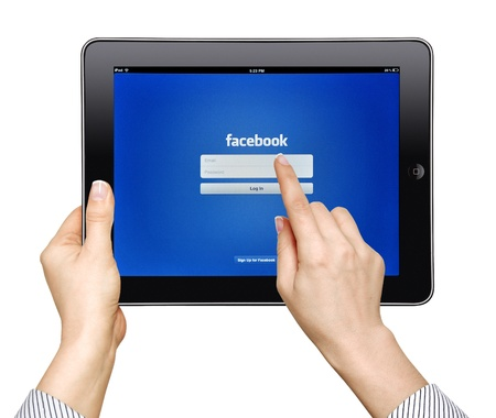 Apple iPad  with facebook app on screen in female hands  Editorial studio shot