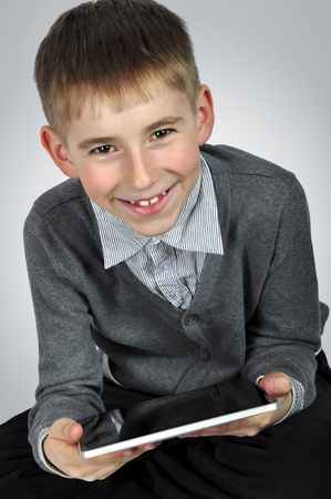 Portrait of a cheerful boy with tablet computer  photo