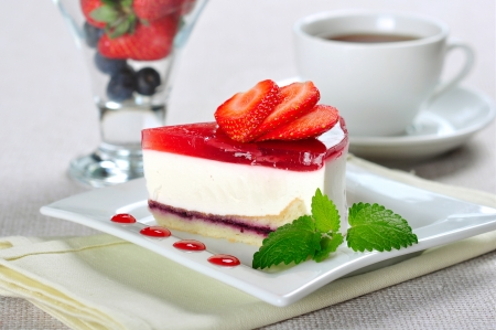a piece of strawberry cheesecake on white plate with coffee cup and berries in glass