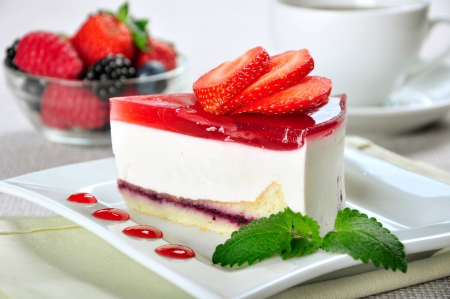piece of strawberry cheesecake on white plate with coffee cup