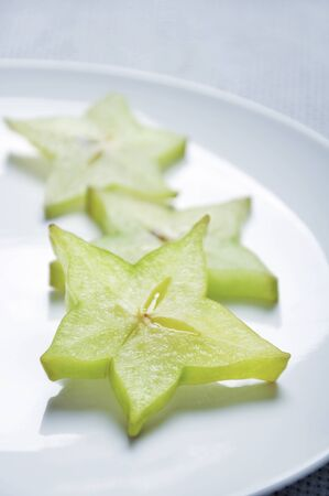 organics: Three slices of carambola on white plate, shallow dof